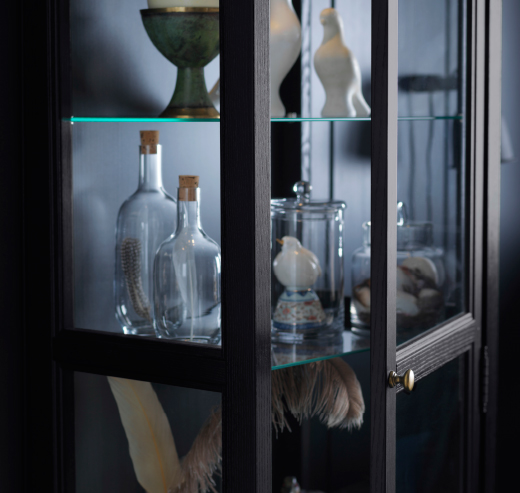 A black gass-door cabinet filled with glass bottles, jars and ceramic birds.