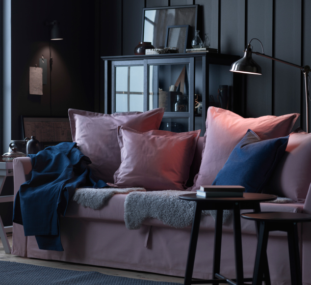 A living room with a light pink three-seat sofa-bed filled with light pink cushions.