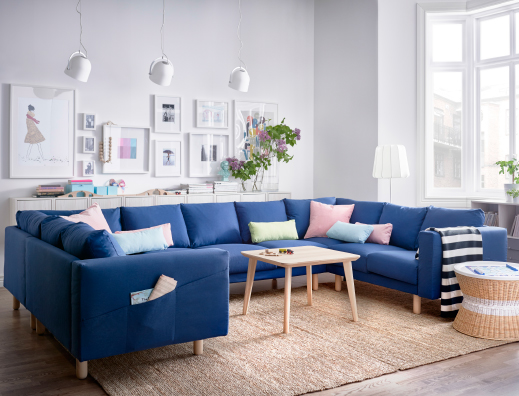 A light living room with a big U-shaped sofa for 9 people, covered with a dark blue fabric. Combined with an ash veneer coffee table and a round rattan tray table with storage inside.