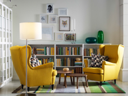 A light living room with two yellow wing chairs, nest of two tables in walnut veneer, white open bookcases and bookcases with glass doors.