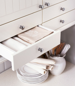 A white opened kitchen drawer with folded white and light pink napkins. Cutlery in a white pitcher, and a stack of porcelain plates are visible below.