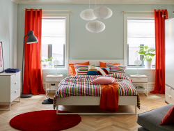 A large bedroom with a white bed for two with bedlinen in orange, red, green, pink and white. Combined with bedside tables, chest of drawers and a wardrobe, all in white with light grey edges.