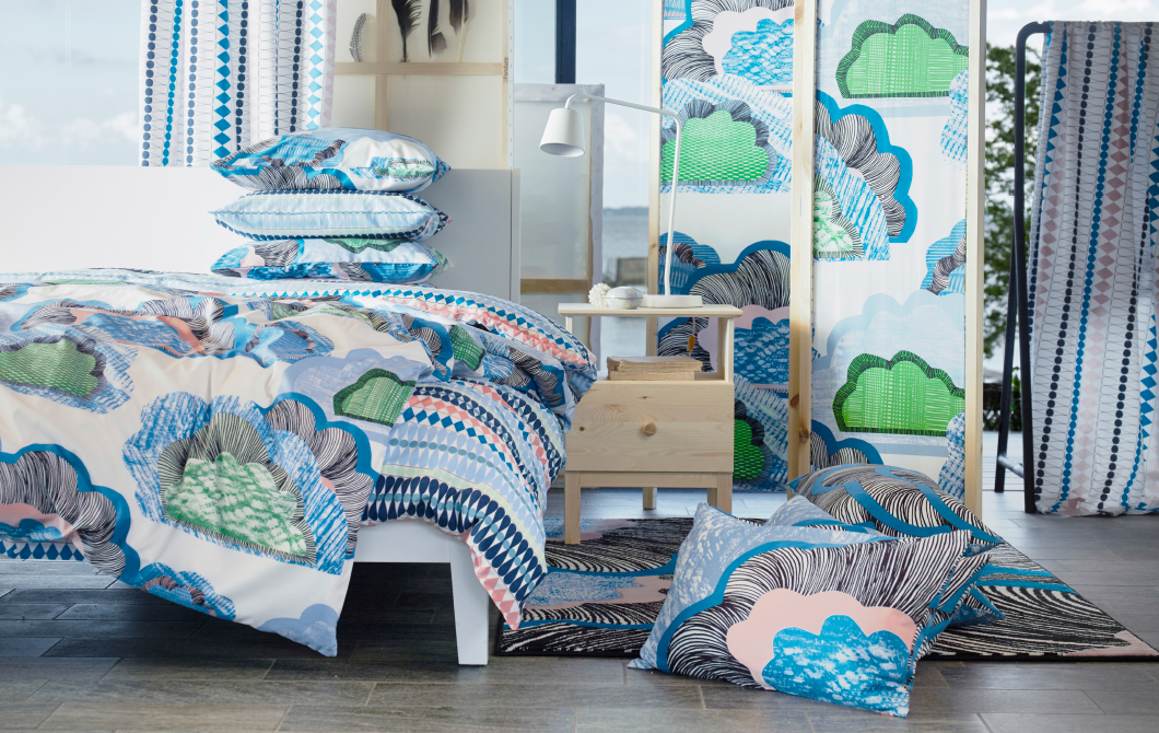 A display of metre fabric, quilt cover and pillowcases with blue/green clouds on a white base.