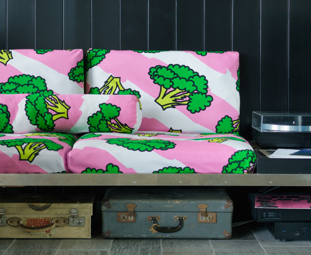 A sofa covered with a white/pink fabric with green broccoli.