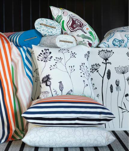 Display of metre fabrics and cushions in striped and different patterns.