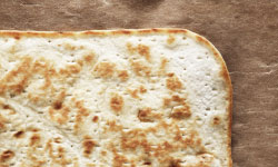 Closeup of the corner of a flatbread. Fry it in a dry pan or grill it.