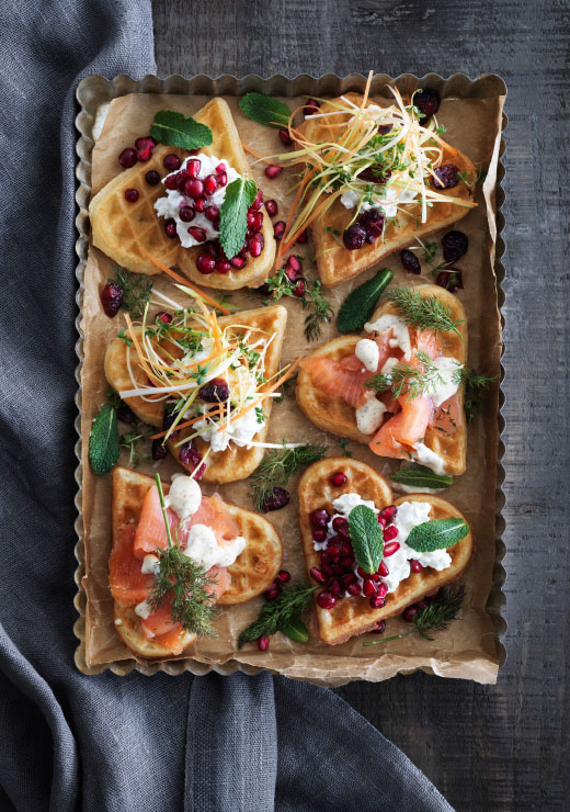A baking tin and parchment paper with heart-shaped waffles placed on top with different toppings, such as lingonberries, cottage cheese, vegetables and marinated salmon.