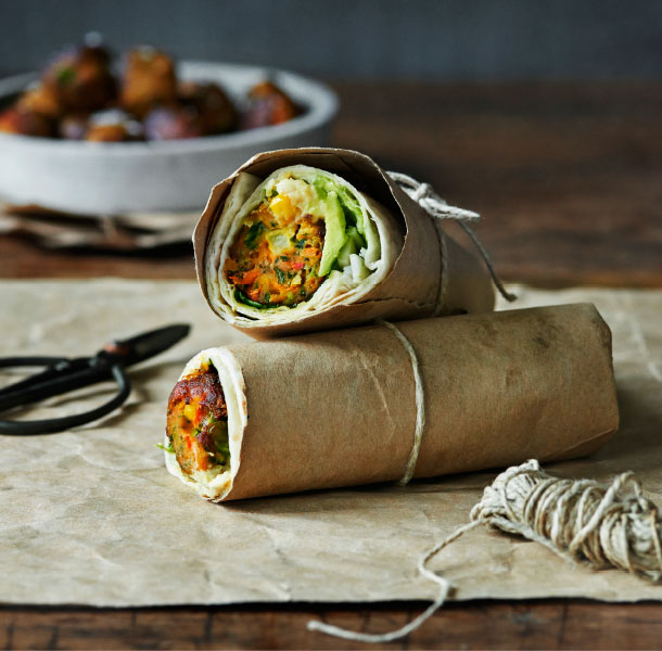 Close up of a veggie ball wrap with avocado, and a pair of sizzors and string next to it.