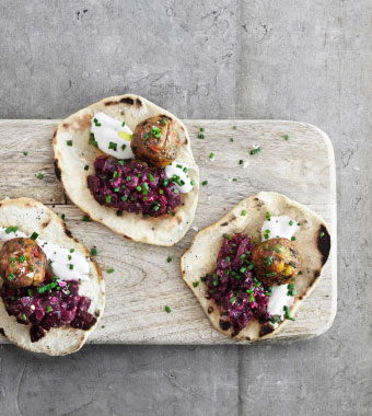 Roasted beet relish and veggie balls with naan bread placed on a wooden cutting board.