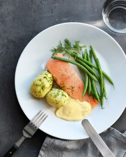 A salmon fillet with green beans, two boiled potatoes and a side of cream sauce on a plate with a fork and knife visible.