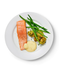 A salmon filé with green beans, two boiled potatoes and a side of cream sauce on a plate with a fork and knife visible.