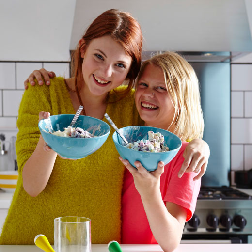 Two teenaged girls standing together, laughing and each holding a bowls of ice cream in front of them