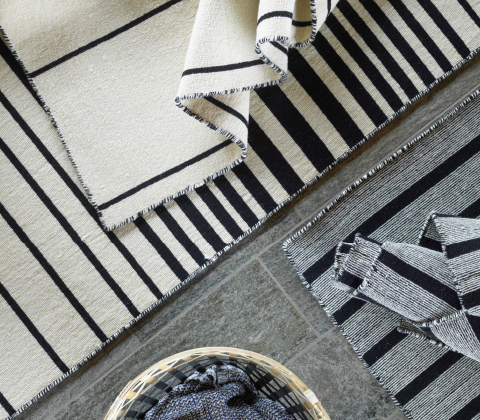 Close-up of an off-white/black striped rug.