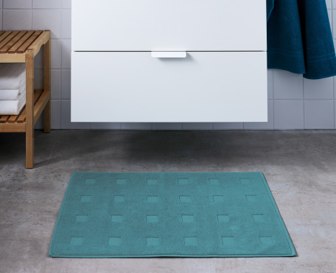 SKOGHALL bathroom rug below a white cabinet.