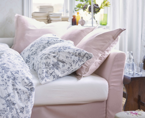 Pink HOLMSUND daybed with blue and white patterened bedding.