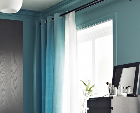 Turquoise SANELA curtains next to a dresser.