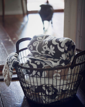 A basket filled with towels in different sizes.