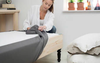 A woman putting on the cover on the sprung mattress base.