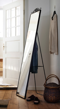 A standing mirror with clothes storage at the back.