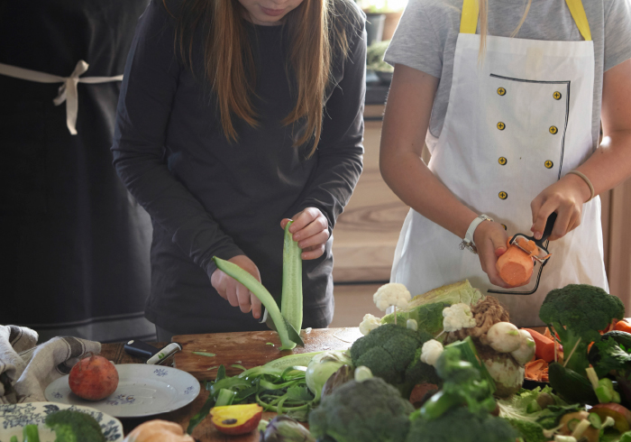 Two girls peeling and cutting vegetables in the kitchen.