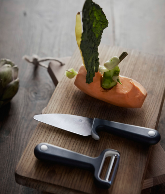 A chopping board with a small knife and a peeler.