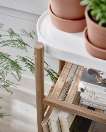 A close-up of a plant stand with bamboo legs and white top shelf.
