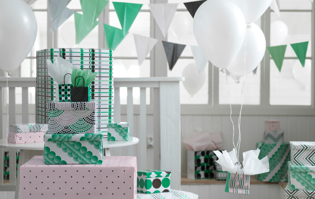 A display of gift wraps and gift bags in green, pink, white and black.
