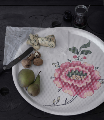A round tray with a floral pattern, shown together with blue cheese, pears and walnuts.