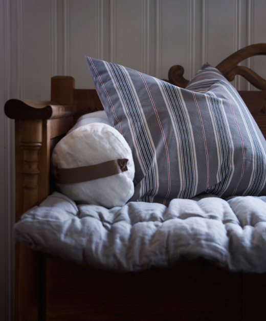 A striped cushion cover in gray, light blue, pink and white.