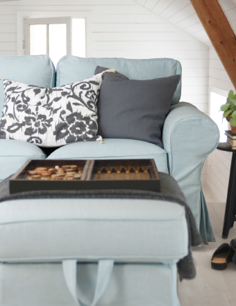 A close-up of a three-seat sofa and footstool in a light blue cover.