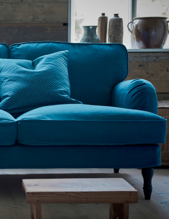A close-up of a three-seat sofa in a turquoise cover.