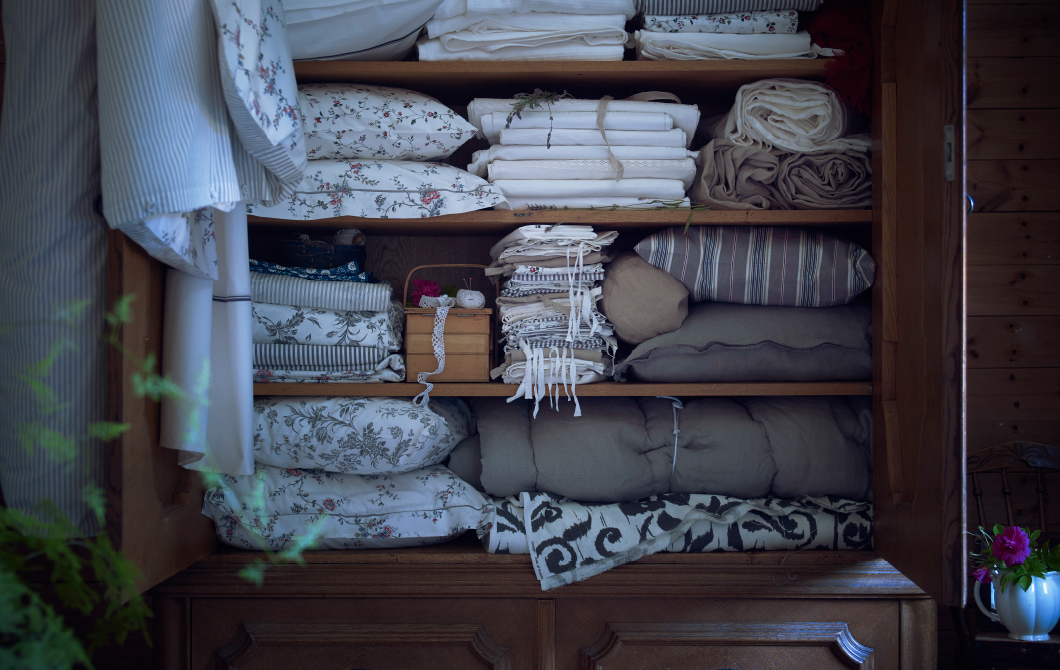 An old cabinet filled with pillowcases, quilt covers, cushions and sheets in beige, grey and white.