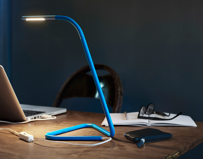 A work lamp made of bent metal pieces, in blue and silver-colour.