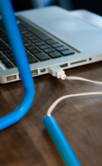 Close-up of a work lamp connected to a laptop through a USB port.