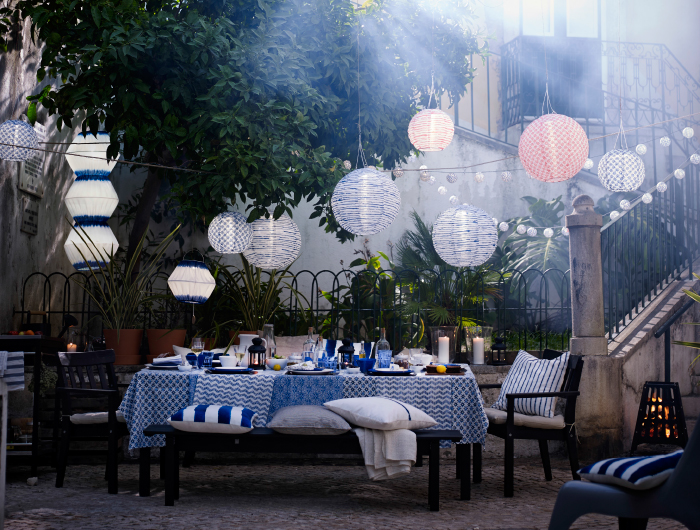A ready laid table in blue and white, shown outside, with round LED solar-powered pendant lamps.