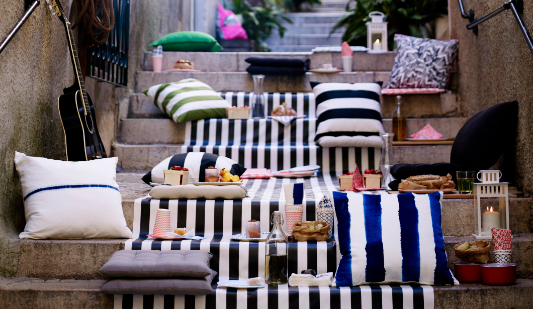 An outdoor picnic with a mix of colourful cushions and fabrics.
