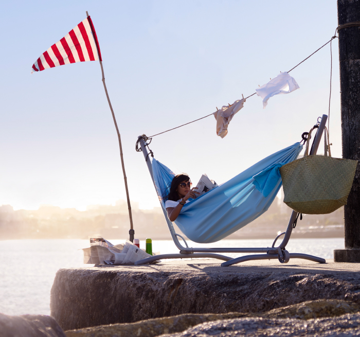 A woman laying in a hammock on a jetty.