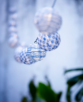 A close-up of small round shades in blue and white on a lighting chain.