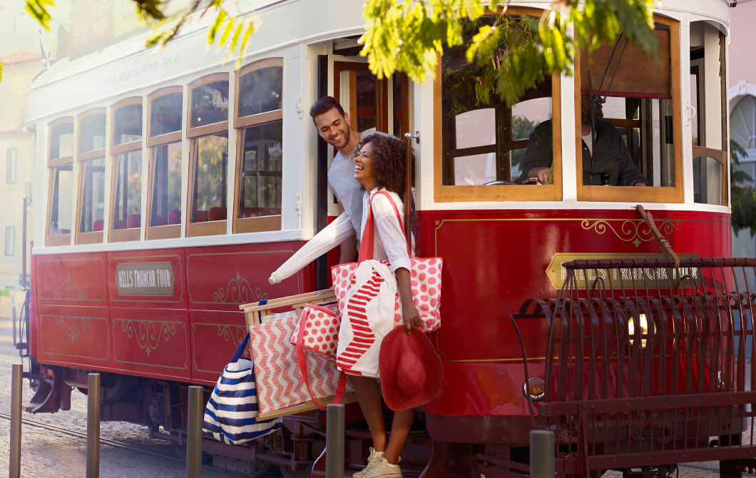 A young couple with beach bags, cool bags and foldable beach chairs riding on a street car.