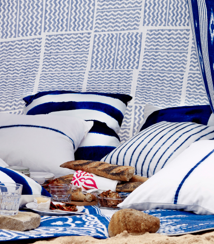 A tent on the beach, made of metre fabric with lots of white/blue cushions inside.
