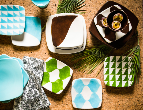 Plates and side plates with brown, light blue and green patterns displayed on a cork background.