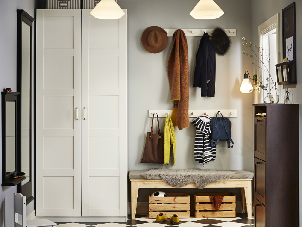 A hallway with a white wardrobe and a brown shoe cabinet that holds at least 12 pairs of shoes. Shown together with a bench in solid pine and four white knob racks.