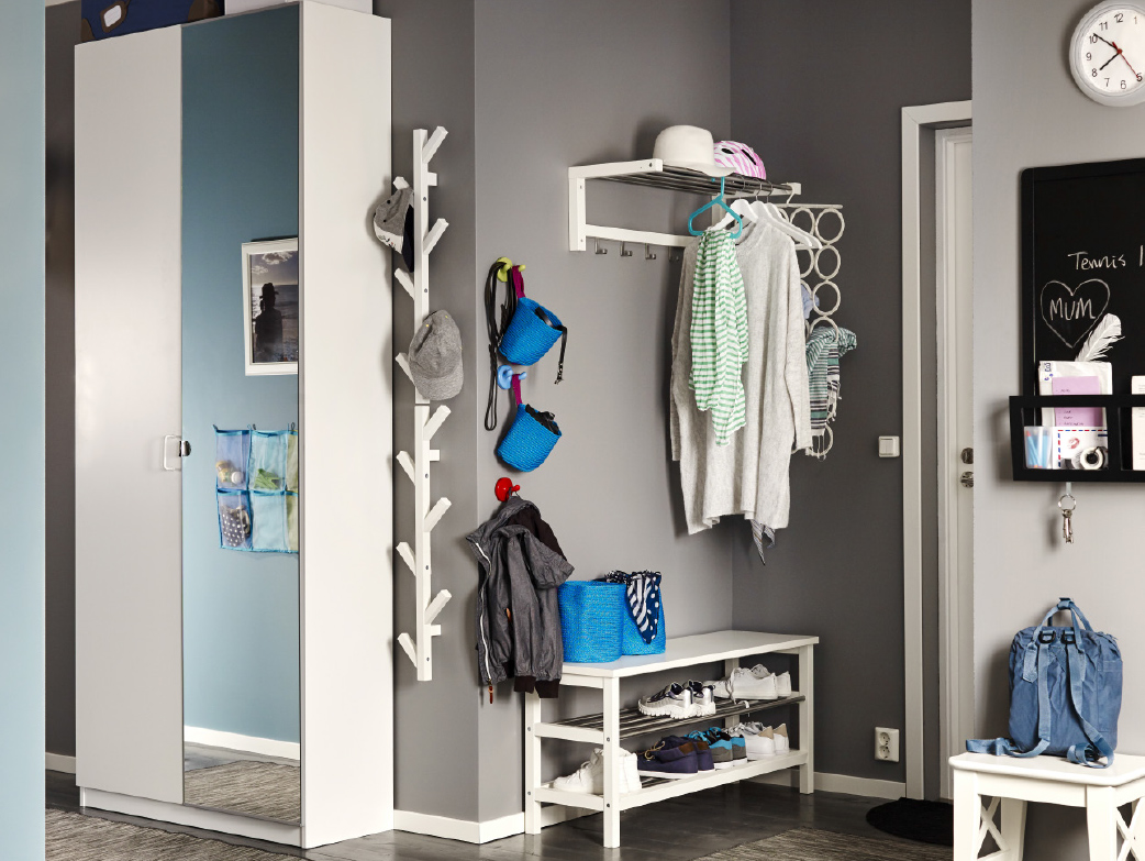 A gray hallway with a white hat rack, a tree-shaped wall hanger and a shoe rack that holds 8 pairs of shoes. Shown together with a wardrobe with one white door and one mirror door.