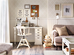 A corner in the living room with a white desk and a swivel chair.
