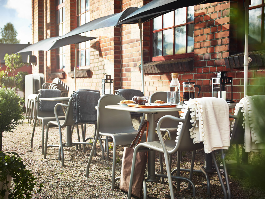 An outdoor bistro with grey stackable armchairs and foldable tables. Combined with black parasols and blankets in white and grey.