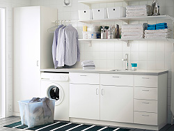 A laundry room with white wall shelves, base cabinets with doors or drawers and a high cabinet with shelves inside