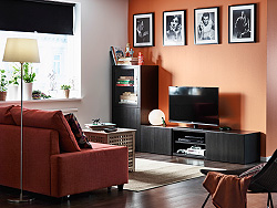 A second TV room with a TV bench in black-brown with drawers, doors and tempered glass door. Shown together with a dark orange corner sofa-bed and a storage table in acacia.