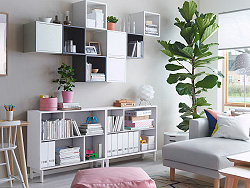 A bright living room with white open shelf unit combined with wall cabinets in white and gray, some with doors and some open.