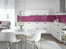 A large white kitchen with integrated pink handles and white worktops. Combined with stainless steel extractor hood, oven and microwave oven.