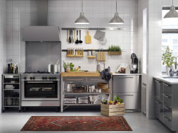 A medium size kitchen in stainless steel with white worktops and stainless steel handles. Combined with stainless steel extractor hood and cooker.